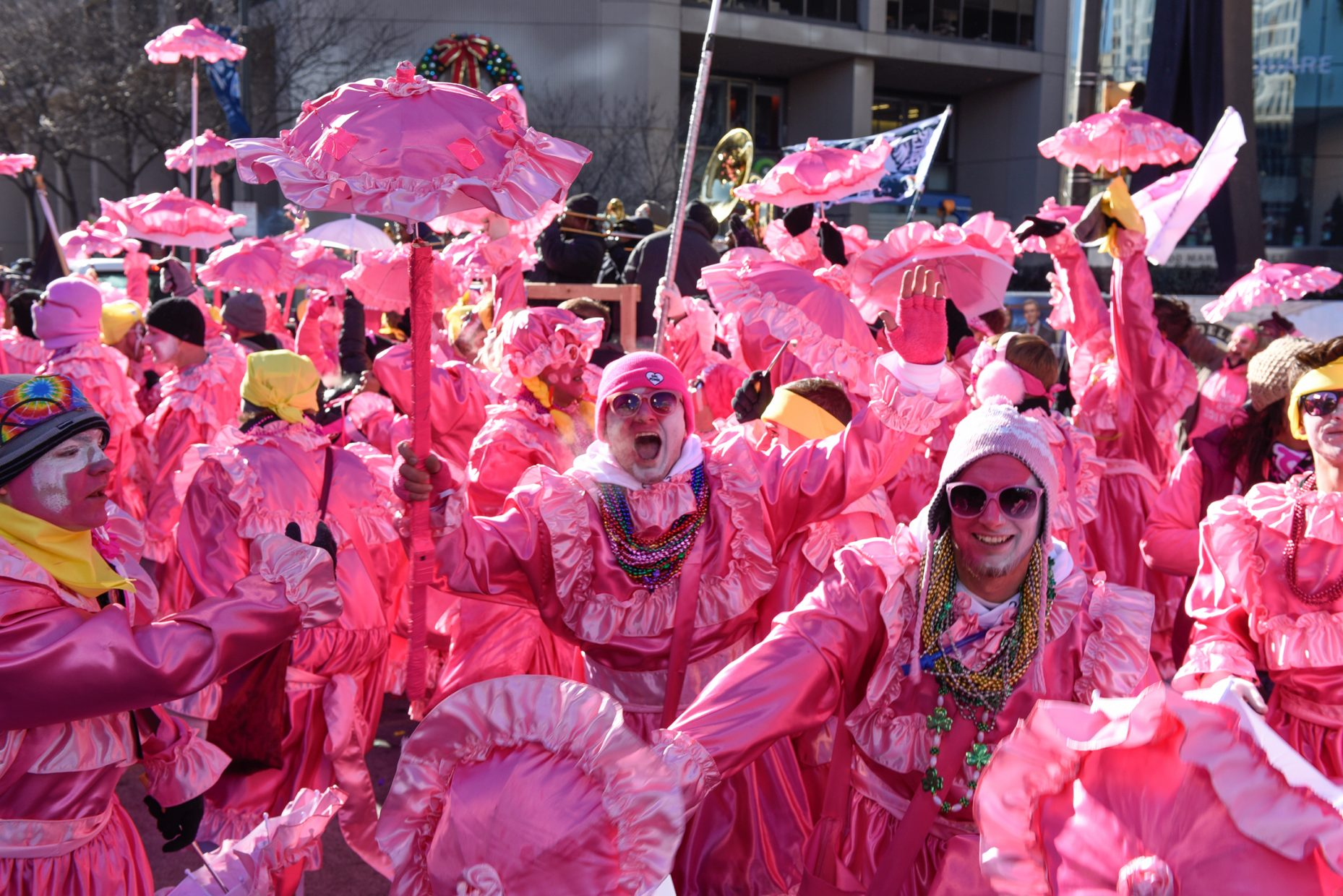Mummers dancing in pink outfits with umbrellas on New Years Day 2018.