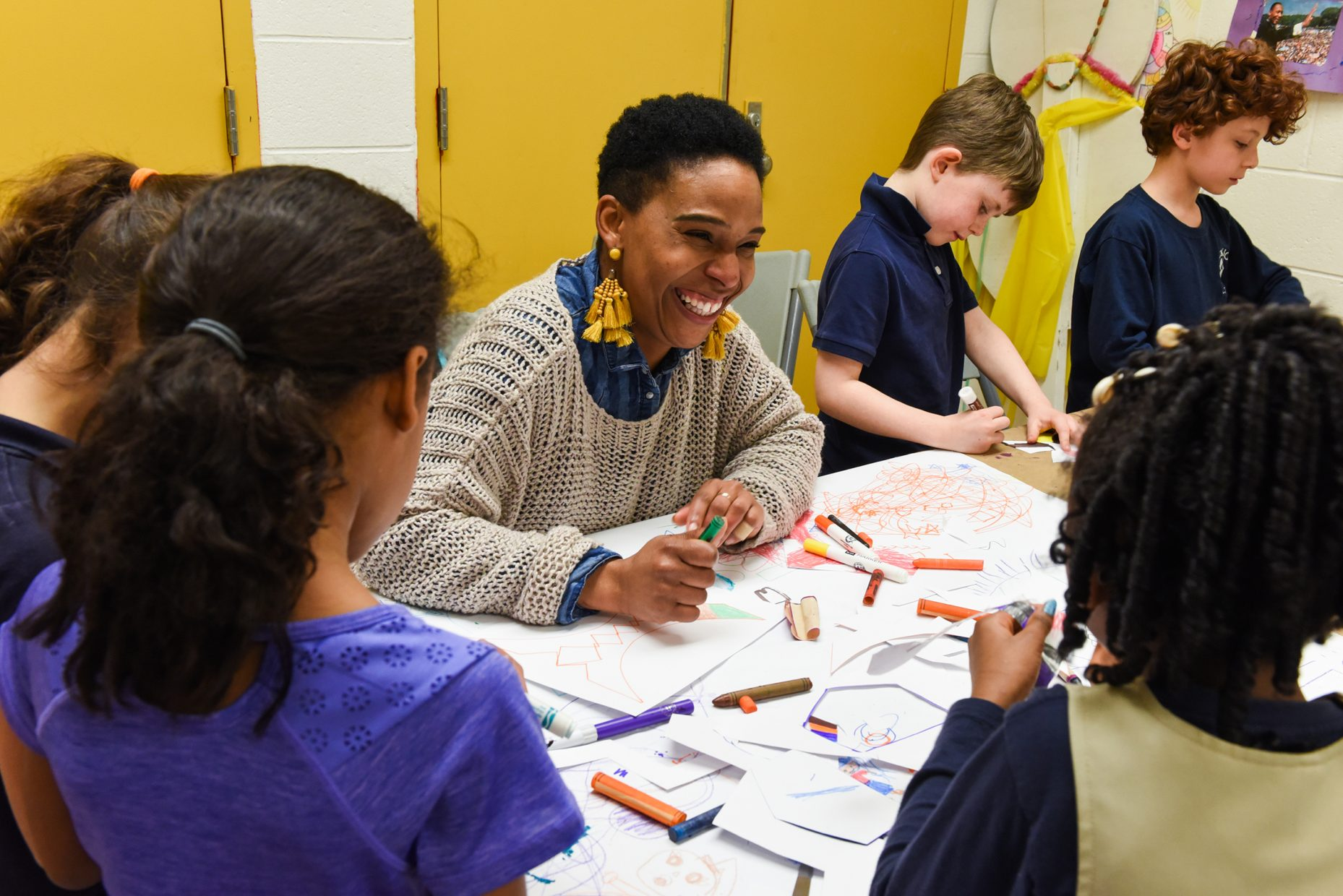 A woman laughs while doing arts and crafts with children.