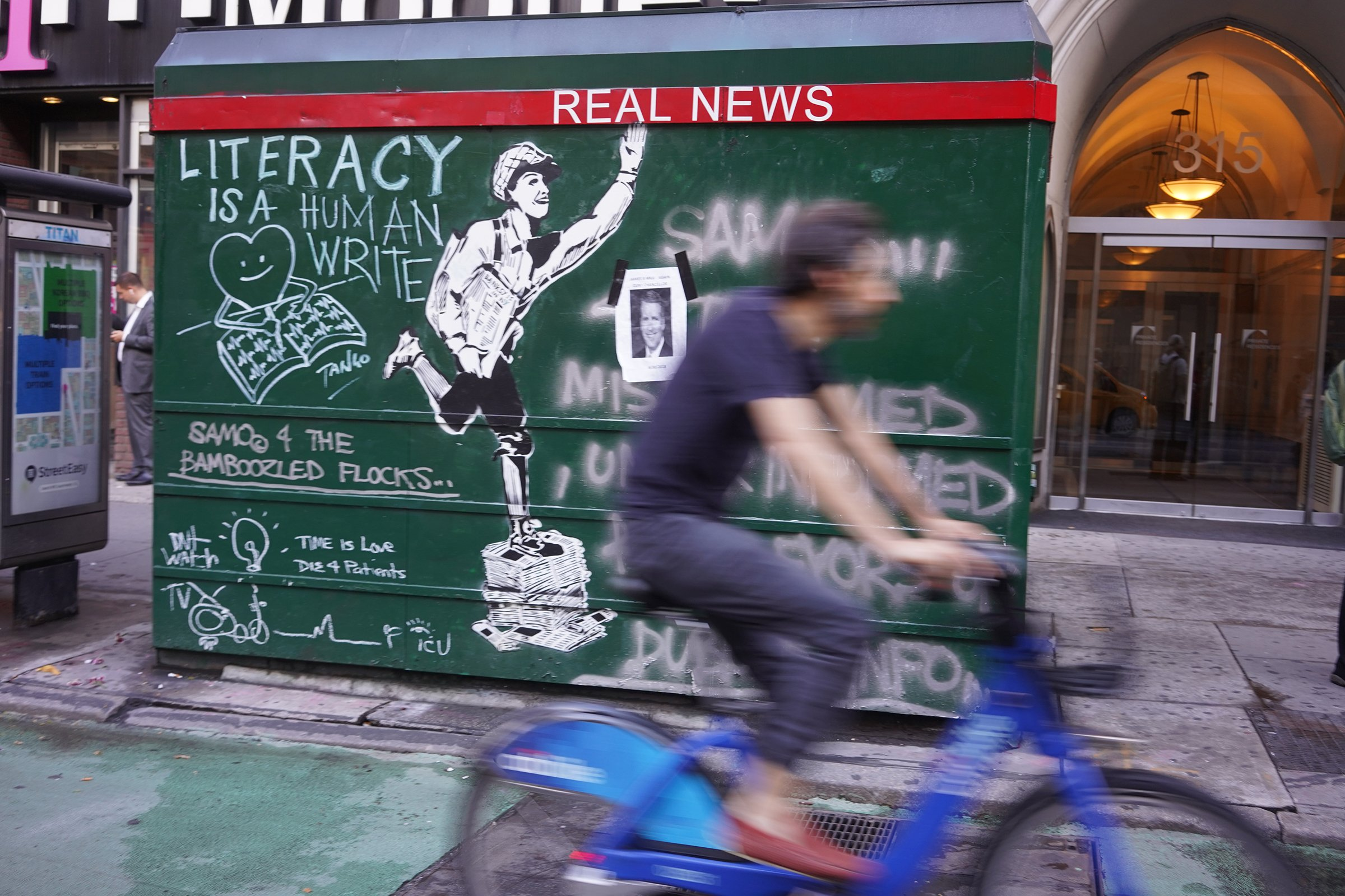 "A man on a bicycle rids past street art that says ""Real News"""