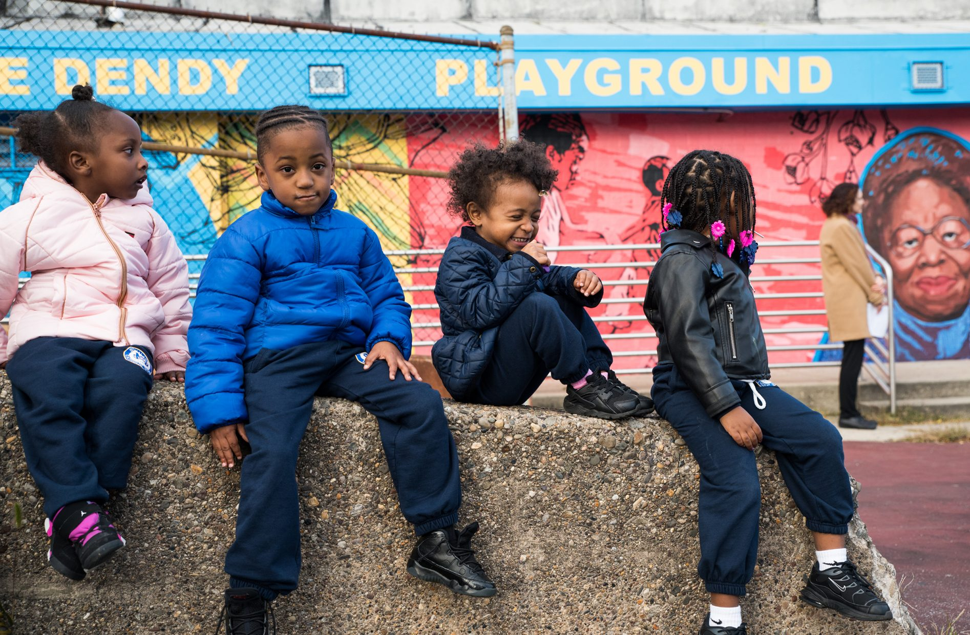 Four children sit on a ledge at the playground in front of a bright mural.