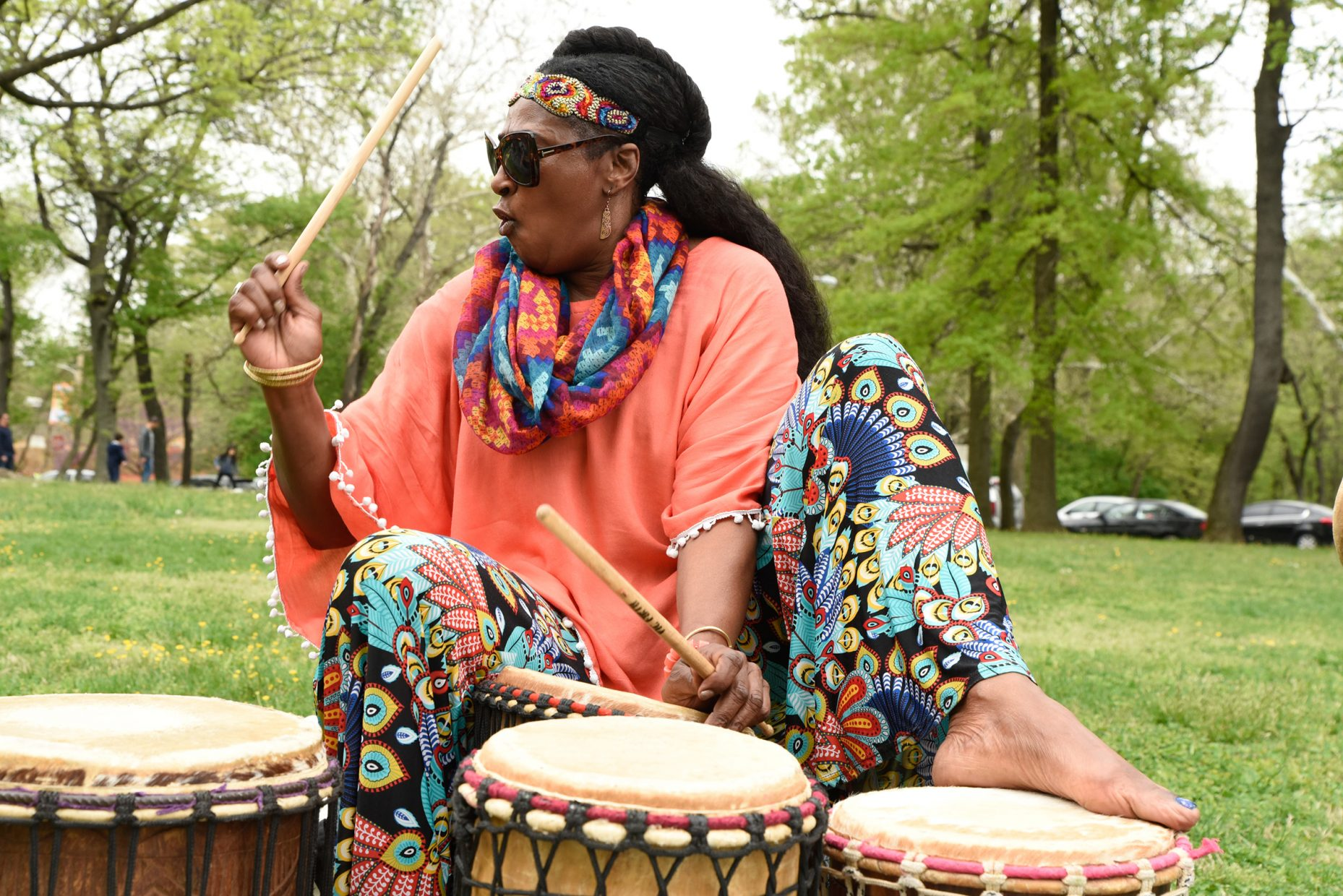 A woman plays the drums with her hands and feet outside.