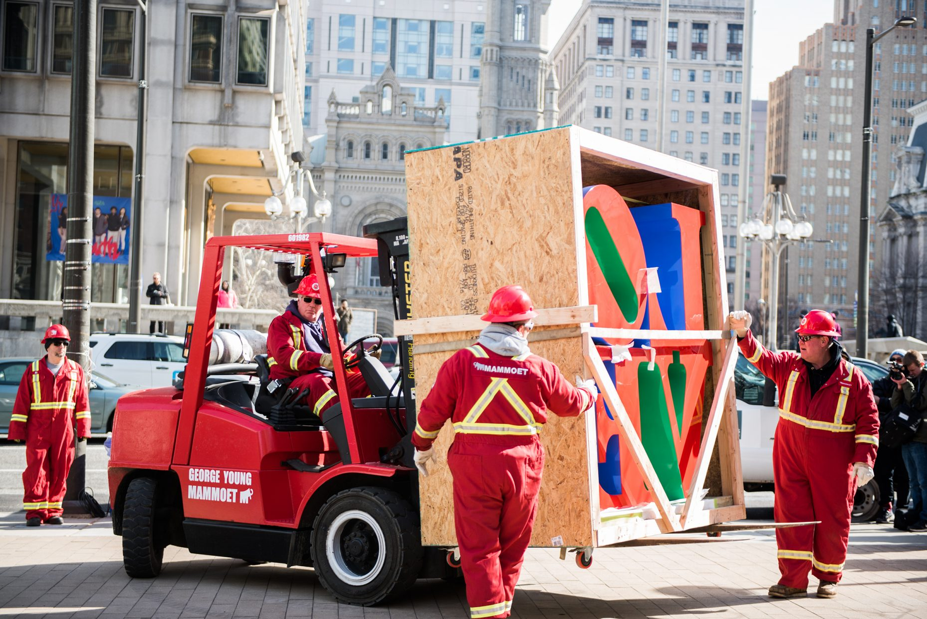 Construction workers use a forklift to transport the LOVE statue in Philadelphia.