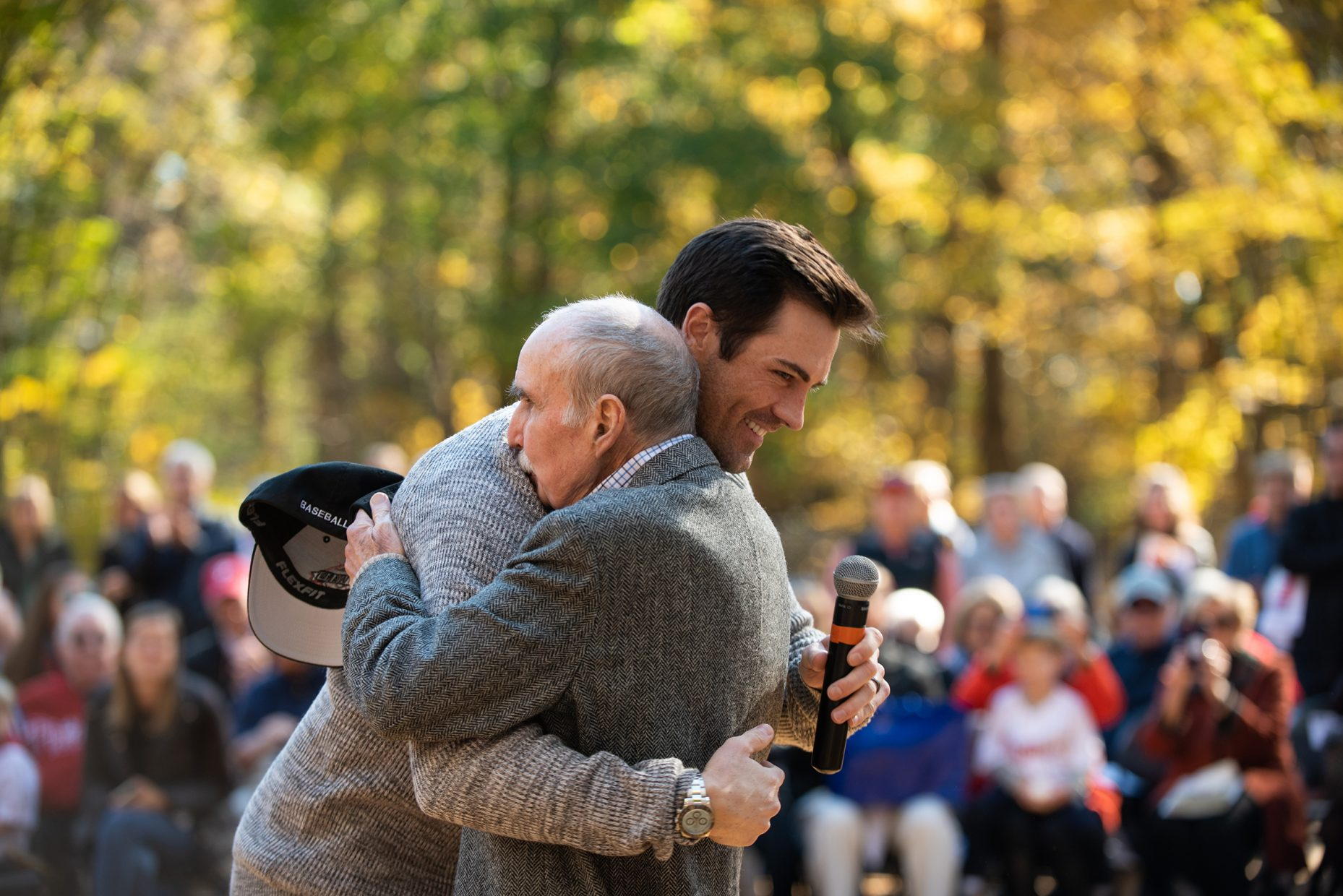 Two men hug on a baseball field in the fall.